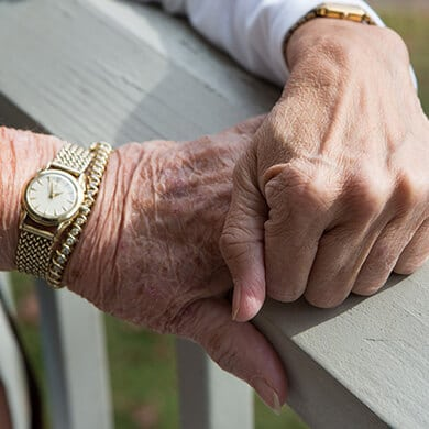 caretaker holding patient's hand